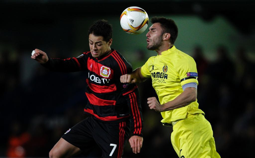 Leverkusen's Mexican forward Chicharito (L) vies with Villarreal's defender Victor Ruiz during the UEFA Europa League Round of 16 first leg football match Villarreal CF vs Bayer Leverkusen at El Madrigal stadium in Vila-real on March 10, 2016.   / AFP PHOTO / JOSE JORDAN