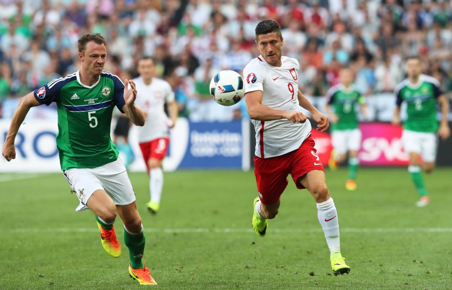 Northern Ireland's Jonny Evans, left, chases Poland's Robert Lewandowski running with the ball during the Euro 2016 Group C soccer match between Poland and Northern Ireland at the Allianz Riviera stadium in Nice, France, Sunday, June 12, 2016. (AP Photo/Thanassis Stavrakis)