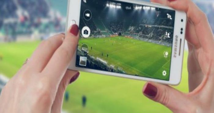 mujer grabando un partido de fútbol con el móvil